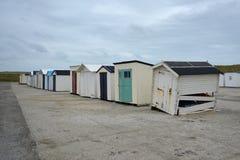 Rad av åtskilliga gamla kasserade och skadade strandskjul på stranden av ön Texel i Nederländerna royaltyfria bilder