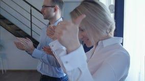 Rad av affärsfolk som applåderar händer efter rapport av högtalaren lager videofilmer