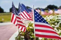 Rad av amerikanska flaggan på gatasidan Fotografering för Bildbyråer