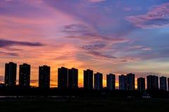 Rad av andelslägenheter på solnedgången med mångfärgad himmel Royaltyfri Foto
