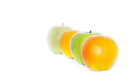 Rad av apelsiner och gräsplanäpplen Fotografering för Bildbyråer