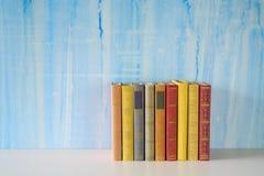 Rad av böcker på grungy bakgrund Arkivbild