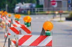 Rad av barrikader för vägtrafik med gula ljus arkivbild