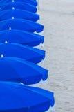 Rad av blåa strandparaplyer Arkivbilder