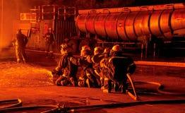 Rad av brandmän i bunkerkugghjulet som förbereder sig att gå in i en eldsvåda Arkivfoton