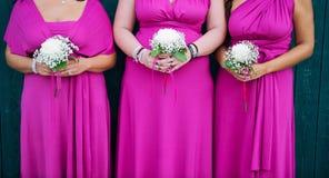 Rad av brudtärnor med buketter på bröllopceremoni Royaltyfria Bilder