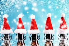 Rad av bruna ölflaskor med jultomtenhattar royaltyfri fotografi