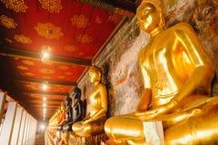Rad av Buddhastatyn med thai konstarkitektur i den kyrkliga Wat Suthat templet Royaltyfri Bild