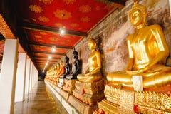 Rad av Buddhastatyn med thai konstarkitektur i den kyrkliga Wat Suthat templet Royaltyfri Foto