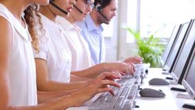 Rad av call centermedel som skriver på deras skrivbord lager videofilmer