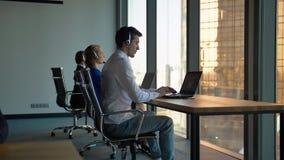 Rad av call centermedel som skriver på deras skrivbord i kontoret lager videofilmer