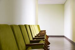 Rad av den gröna salongen som placerar mjuka stolar med handstilblock som förläggas längs väggen i hallet Affär eller politisk hä arkivfoton