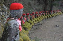 Rad av den japanska Buddha som bär den röda halsduken, Jizo statyer arkivfoton