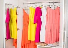 Rad av den ljusa färgrika klänningen som hänger på laghängare, skor och H Royaltyfria Bilder