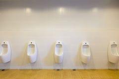 Rad av den offentliga toaletten för utomhus- pissoarmän, vita pissoar för Closeup I fotografering för bildbyråer