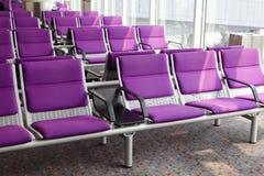 Rad av den purpura stolen på flygplatsen Arkivbilder