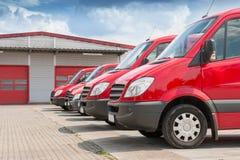 Rad av den röda leveransen och tjänste- bilar royaltyfri foto