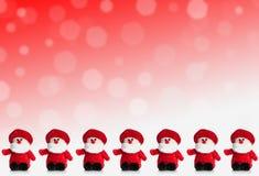 Rad av dockor av Santa Claus på en röd bakgrund med snö Royaltyfri Foto