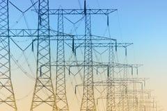 Rad av elektricitetspylons Arkivbild