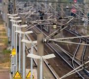 Rad av elektriska lyktor bredvid pantographs på en plattform bredvid stängerna av järnvägen arkivfoton