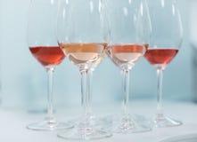Rad av exponeringsglas med vit och rosa viner som är förberedda för degustatio Royaltyfria Bilder