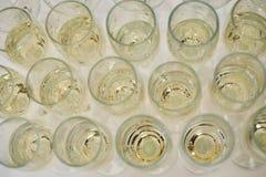 Rad av exponeringsglas som fylls med vitt vin för kall champagne royaltyfri bild