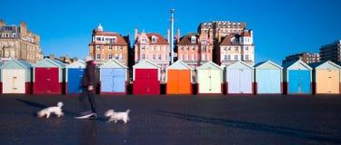 Rad av färgglade strandkojor, hus bakom, man som går två med Fotografering för Bildbyråer