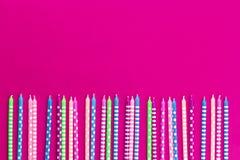 Rad av färgrika stearinljus på rosa bakgrund för neon arkivbilder