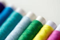 Rad av färgrika trådrullar på tabellen Fotografering för Bildbyråer
