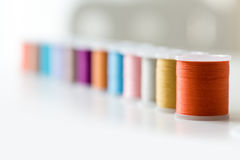 Rad av färgrika trådrullar på tabellen Royaltyfri Bild