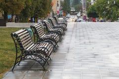 Rad av fem bänkar på gatan i regnet Royaltyfri Foto