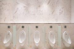 Rad av fem pissoar med den infraröda avkännaren, på marmorväggen, i mäns offentliga toalett Arkivfoton