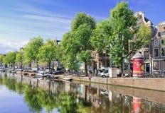 Rad av forntida renoverade herrgårdar nära en kanal, Amsterdam, Nederländerna Arkivfoto