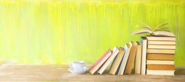Rad av gamla böcker och en kopp kaffe på en lantlig bokhylla royaltyfri fotografi