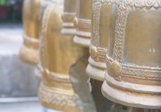 Rad av gamla klockor i buddistisk tempel Arkivfoto