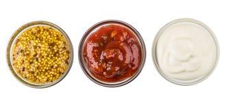 Rad av glass bunkar med senap, tomatketchup och majonnäs royaltyfria foton