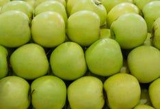 Rad av gröna äpplen Arkivfoton
