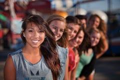 Rad av gulliga flickor på nöjesfält Arkivfoton