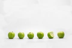 Rad av hela gröna äpplen med ätit ett Royaltyfri Foto
