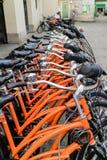 Rad av identiska orange cyklar Arkivfoto