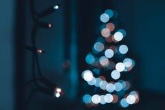 Rad av julljus som hänger på väggen, med det defocused xmas-trädet i bakgrunden Abstrakt bakgrund arkivbild