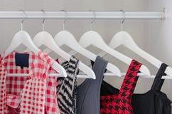 Rad av klänningen som hänger på laghängare Arkivbild