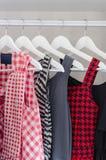Rad av klänningen som hänger på laghängare Arkivfoton