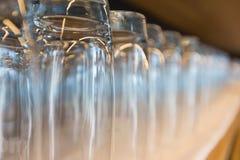 Rad av klara högväxta dricka exponeringsglas Arkivfoto