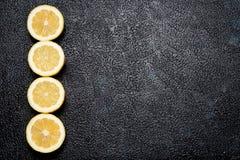 Rad av klippta citroner på mörk bakgrund med utrymme för din text Arkivfoton