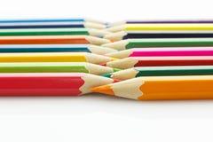 Rad av kulöra blyertspennor, på vit bakgrund Royaltyfria Foton