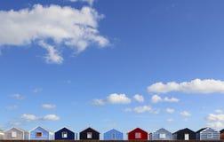 Rad av ljust färgade strandkojor royaltyfri fotografi