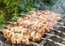 Rad av metallsteknålar med varmt grillat kött arkivbilder
