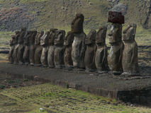 Rad av Moai mot berget Royaltyfria Bilder