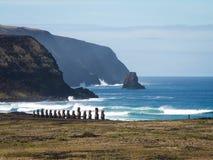 Rad av Moai vid havslandskap Royaltyfri Bild